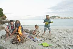 Spain, Mallorca, Friends at camp fire on beach - stock photo