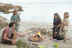 Spain, Mallorca, Friends grilling sausages at camp fire on beach Stock Photos