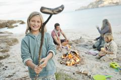 Spain, Mallorca, Friends with sausages at camp fire on beach Stock Photos