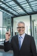 Germany, Stuttgart, Businessman with one finger, smiling, portrait Stock Photos