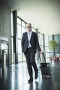 Stock Photo of Germany, Stuttgart, Businessman pulling luggage in office building
