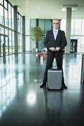 Germany, Stuttgart, Businessman standing with luggage in office building - stock photo