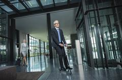 Germany, Stuttgart, Businesswoman with wheeled luggage, man riding scooter at - stock photo