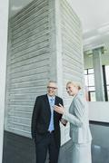Stock Photo of Germany, Stuttgart, Business people in office lobby, smiling