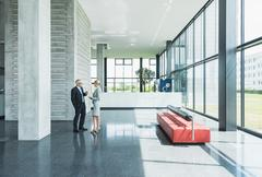 Germany, Stuttgart, Business people having discussion at office lobby - stock photo