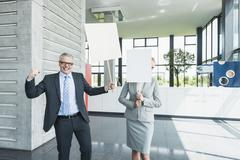 Germany, Stuttgart, Business people holding blank signs in office lobby, smiling - stock photo