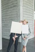 Germany, Stuttgart, Business people holding blank signs in office lobby, kissing - stock photo