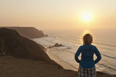 Portugal, Algarve, Senior woman looking at sunrise Stock Photos