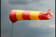 Stock Video Footage of Wind sock with rainy stormy clouds background. Red and yellow, click for HD