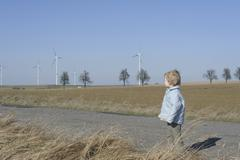 Germany, Saxony, Boy standing on road, wind turbine in background Stock Photos