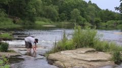 Washing hands in river Stock Footage