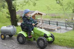 Germany, Bavaria, Boy sitting in toy tractor with trailer - stock photo