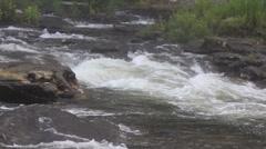 Rapids flowing past large rocks - stock footage