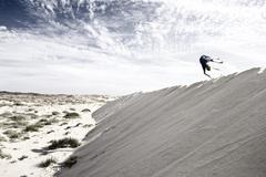 Stock Photo of France, Boy jumping on sand dune