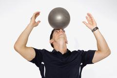 Stock Photo of Personal trainer balancing ball on forehead, close up
