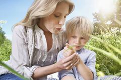 Germany, Cologne, Mother blowing finger of son - stock photo