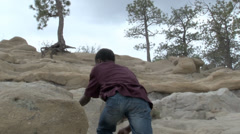 Boy meandering up rock formation. - stock footage