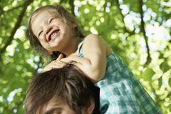 Stock Photo of Germany, Cologne, Father carrying daughter on shoulders, smiling