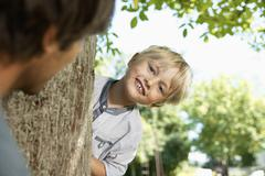 Germany, Cologne, Father and son playing head and seek, smiling Stock Photos