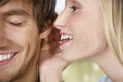 Germany, Cologne, Young woman whispering to man, close up Stock Photos
