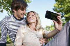 Germany, Cologne, Young couple taking self photograph, smiling - stock photo