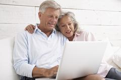 Stock Photo of Spain, Senior couple checking emails on laptop, smiling