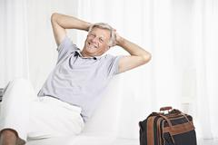 Stock Photo of Spain, Senior man waiting in lobby with suitcase