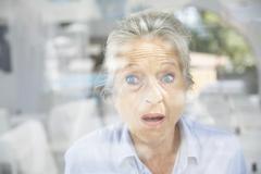Spain, Mallorca, Senior woman behind window - stock photo