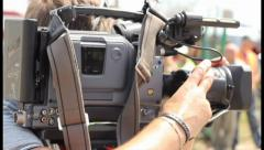 TV operator camera shoots report shots at day time, zooming, click for HD Stock Footage