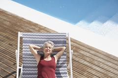 Spain, Senior woman relaxing on deck chair at beach - stock photo