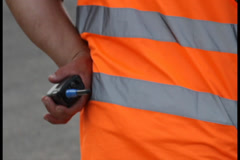 Clumsy security with walky-talky in orange uniform standing, click for HD Stock Footage