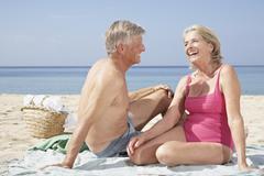 Stock Photo of Spain, Mallorca, Senior couple sitting at beach
