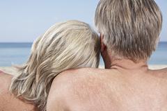 Spain, Mallorca, Senior couple sitting at beach - stock photo