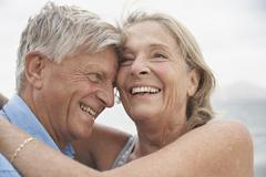 Spain, Mallorca, Senior couple embracing on beach - stock photo