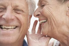 Stock Photo of Spain, Senior woman whispering into ear of man, smiling