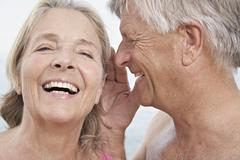 Stock Photo of Spain, Senior man whispering into ear of woman, smiling