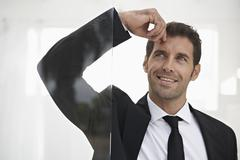 Spain, Businessman standing by door, thinking - stock photo