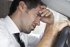 Spain, Dispressed businessman driving car - stock photo