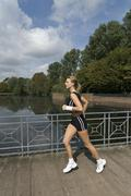 Germany, North Rhine-Westphalia, Duesseldorf, Young woman running in park Stock Photos