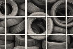 Metal cage full of old automobile tires. Stock Photos