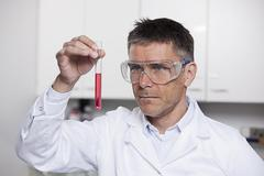 Germany, Bavaria, Munich, Scientist holding red liquid in test tube for medical Stock Photos