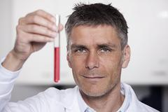 Germany, Bavaria, Munich, Scientist holding red liquid in test tube for medical - stock photo
