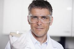 Germany, Bavaria, Munich, Scientist holding liquid in petri dish for medical Stock Photos