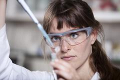 Germany, Bavaria, Munich, Scientist with pipette and test tube in laboratory - stock photo
