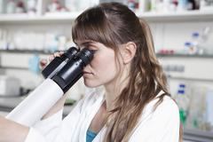 Stock Photo of Germany, Bavaria, Munich, Scientist with microscope in laboratory