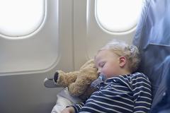 Germany, Boy sleeping in plane Stock Photos