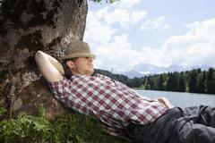 Germany, Bavaria, Mid adult man lying on grass under tree - stock photo