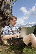 Stock Photo of Germany, Bavaria, Mid adult man using laptop under tree