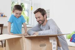 Germany, Berlin, Father and son opening parcel box Stock Photos