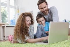 Germany, Berlin, Family using laptop on floor Stock Photos